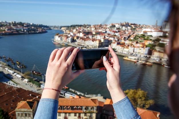 Девушка фотографирует панораму города порту, португалия. мобильная фотография