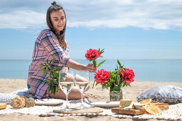소녀는 해변에서 쉬고있다. 해변의 모래 사장에서 낭만적 인 피크닉. 여름 휴가의 개념.
