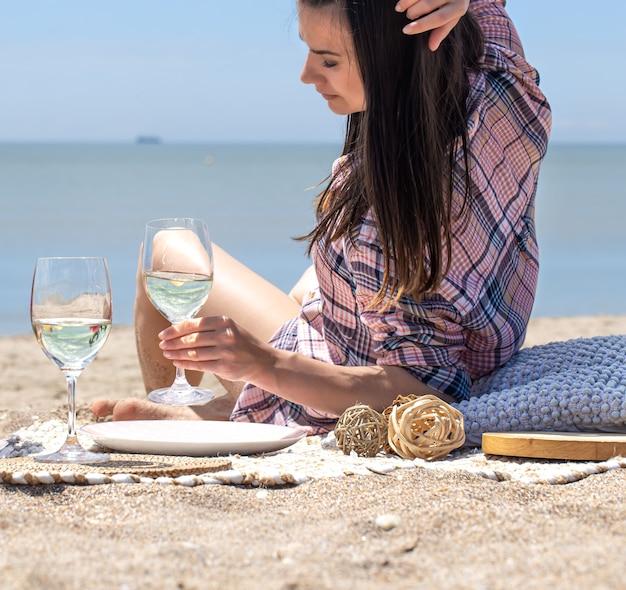 女の子がビーチで休んでいます。ビーチの砂浜でのロマンチックなピクニック。夏休みのコンセプト。