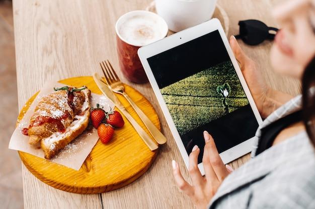 カフェに座ってタブレットを見ている女の子、コーヒーショップの女の子が笑顔で計画を立てています。テーブルにはお菓子があります。