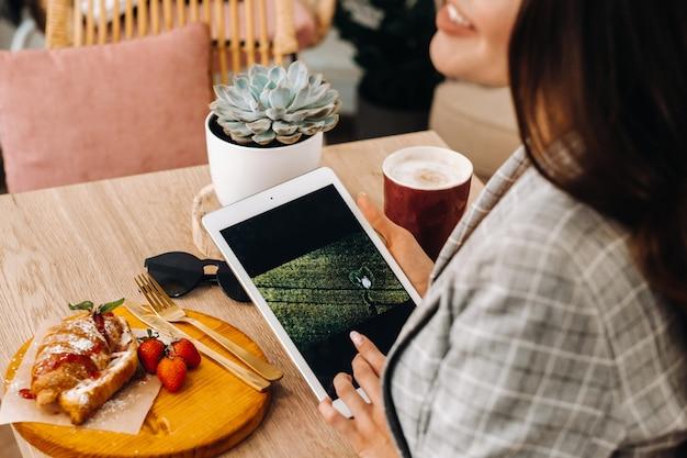 女の子がカフェに座ってタブレットを見ている、コーヒーショップの女の子が笑っている、物事を計画している。テーブルの上にお菓子があります。