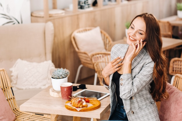 女の子がカフェに座って電話で話している、コーヒーショップの女の子が笑顔でスマートフォンで燃えている、お菓子がテーブルにある