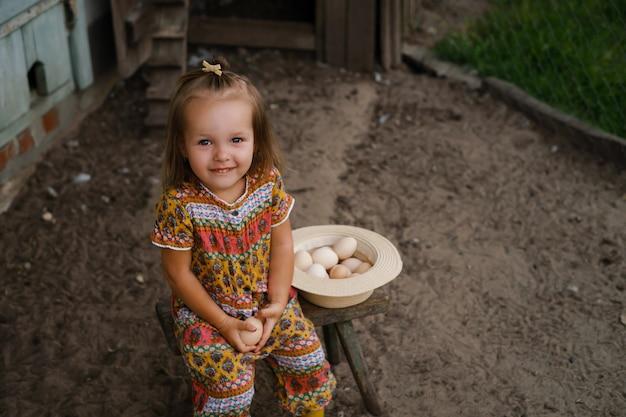 한 소녀가 닭장 근처의 의자에 앉아 손에 닭고기 달걀을 들고 있다
