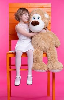 巨大なおもちゃのクマと一緒に高い椅子に座っている女の子