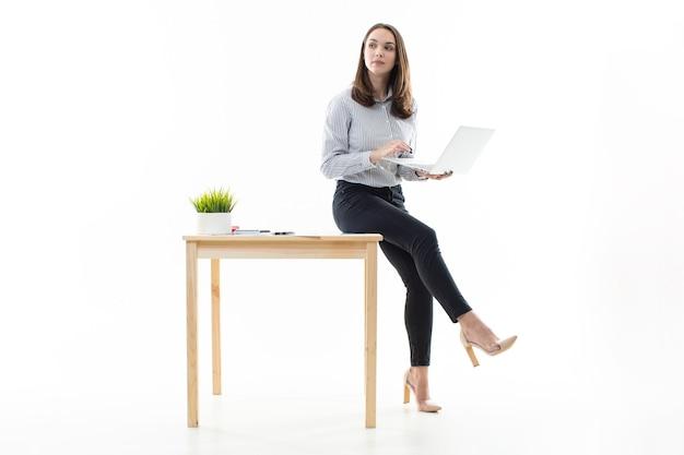 Девушка сидит на столе и печатает на компьютере на белом фоне