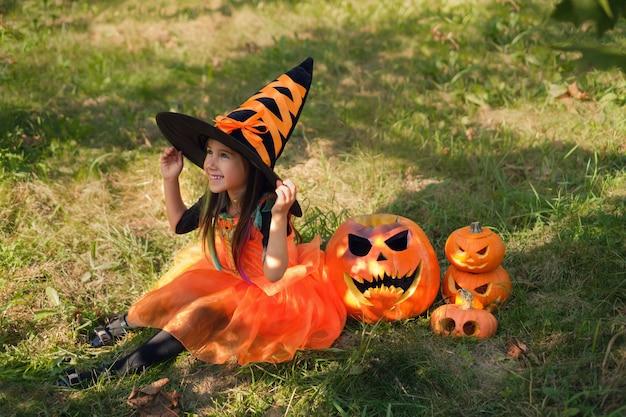 女の子はオレンジ色の魔女の衣装で草の上に座って、彼女の帽子を持っています