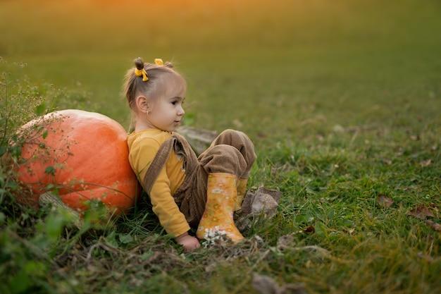 한 소녀가 큰 호박에 등을 대고 땅에 앉아 있다