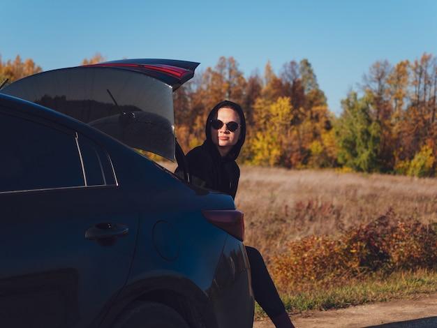 여자는 가을 숲의 배경에 대해 도로에 검은 세단 자동차의 트렁크에 앉아있다.