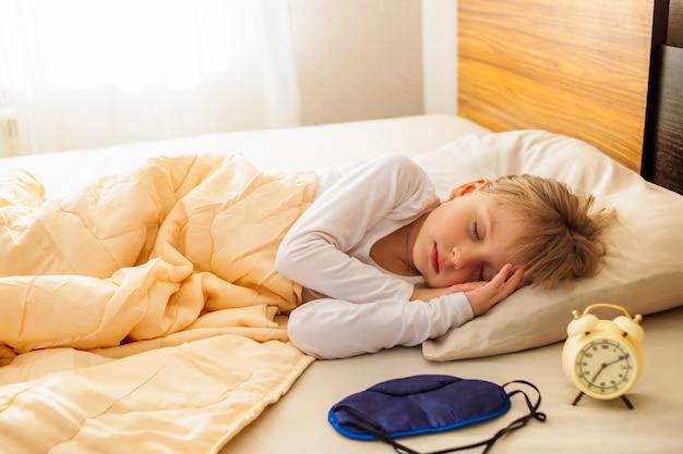 早朝、女の子がベッドで寝ていて、窓と目覚まし時計の横に太陽が輝いています。健康的な睡眠。