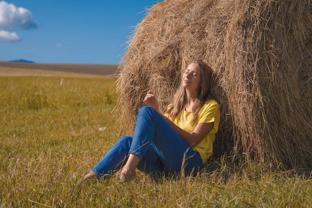 女の子が干し草で日光浴をしています。村の生活:冬の干し草の収穫。動物飼料。