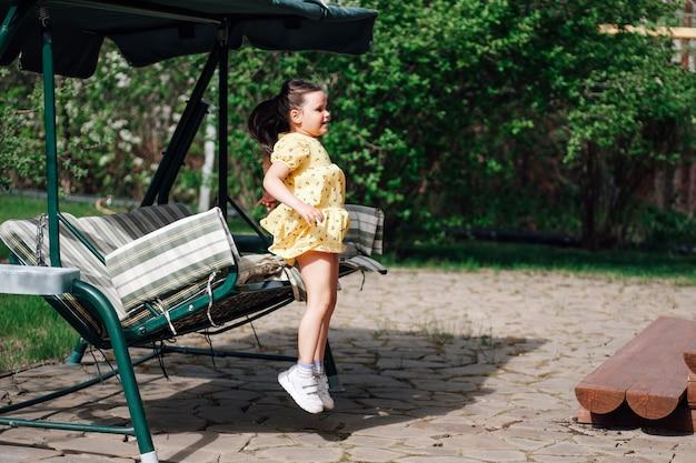 뒤뜰 여름정원 정원그네에서 뛰어내리는 소녀의 움직임과 순간...