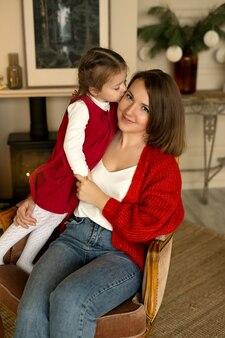 クリスマスイブに女の子が暖炉のそばの肘掛け椅子に座っている母親にキスします
