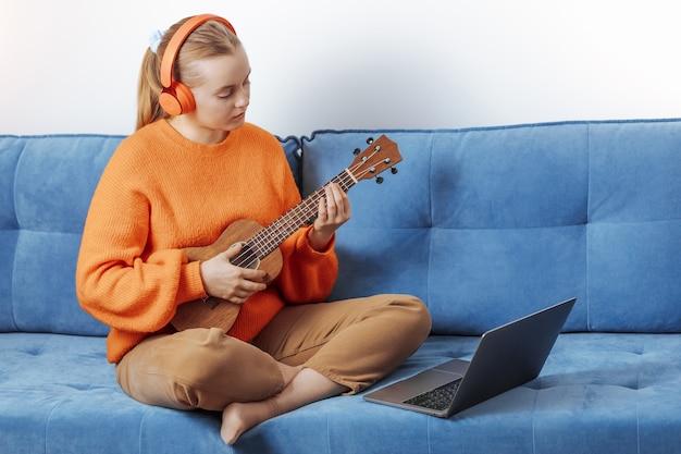 Девушка учится удаленно играть на гавайской гитаре