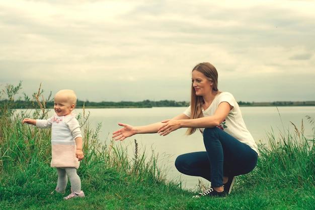女の子は自然の中で母親と一緒に歩くことを学びます。ママと娘、学習と発達。子の最初のステップ。人生の幸せな瞬間。