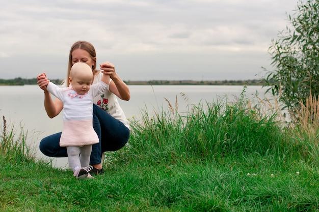 女の子は自然の中で母親と一緒に歩くことを学びます。