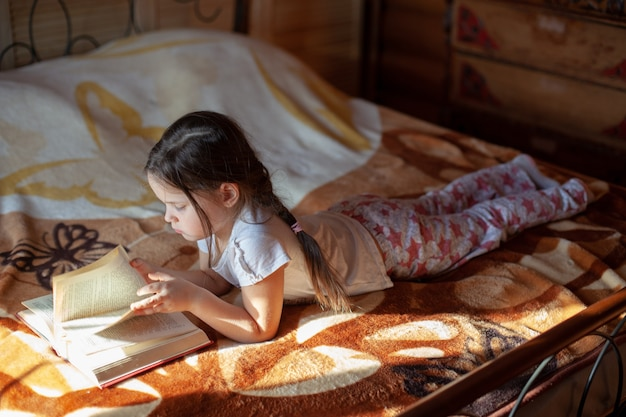 Девушка лежит животом на одеяле на кровати и читает книгу