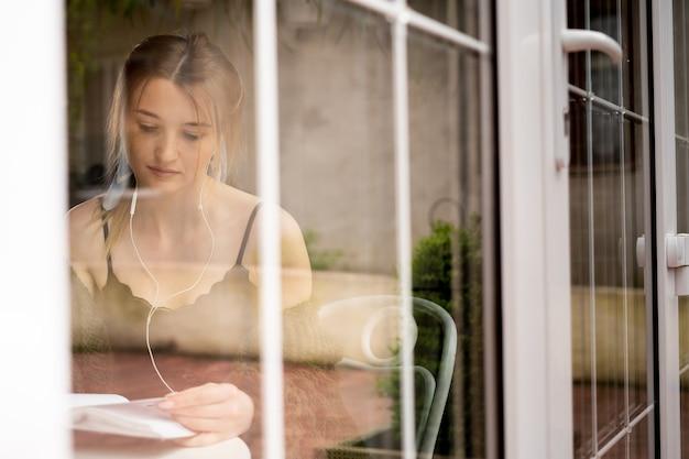 한 소녀가 카페 창가에 앉아 헤드폰을 끼고 오디오북을 듣고 있습니다. 유선 헤드셋을 끼고 식당에 앉아 있는 젊은 여성의 모습. 음악을 듣고 백인 여자입니다. 외부 모습