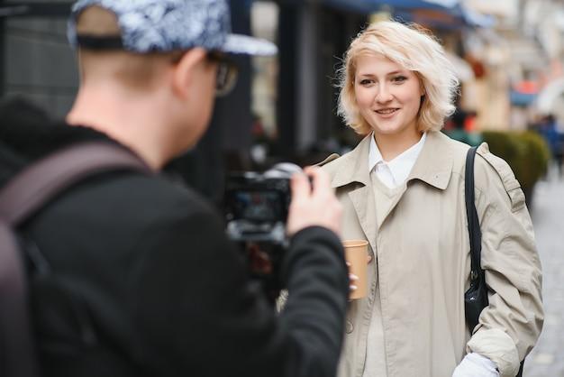 Девушка ведет видеоблог с оператором на улице