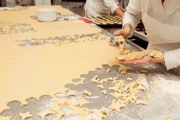 한 소녀가 빵집에서 큰 반죽 조각으로 쿠키 틀을 만듭니다.