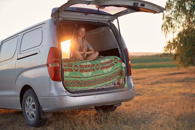 夕焼けの高さを背景に、野原の車に座って蓮華座で瞑想する少女...