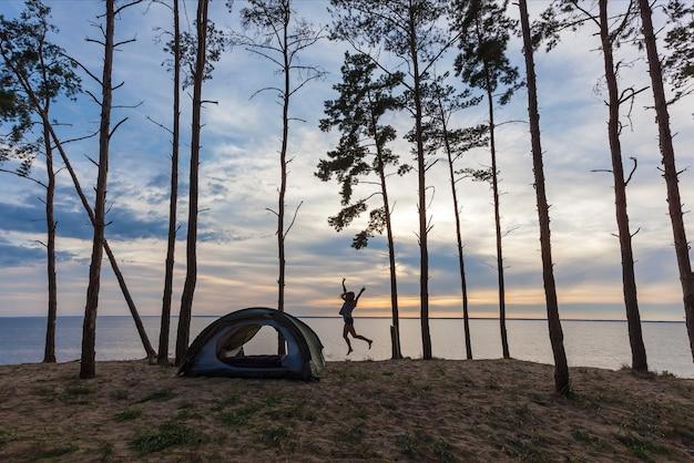 水と森を背景にテントの近くの女の子。テントの近くの女の子。