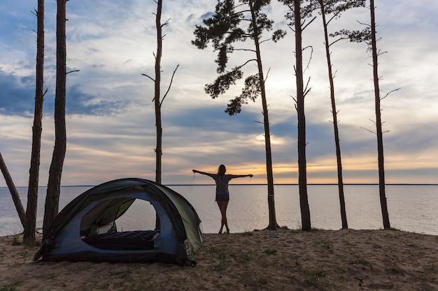 水と森を背景に両手を離してテントの近くにいる女の子。テントの近くの女の子。