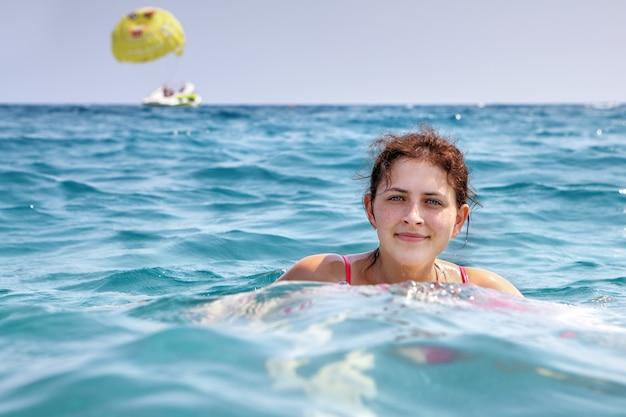 Девушка 19 лет, одна плавает в синей морской воде.
