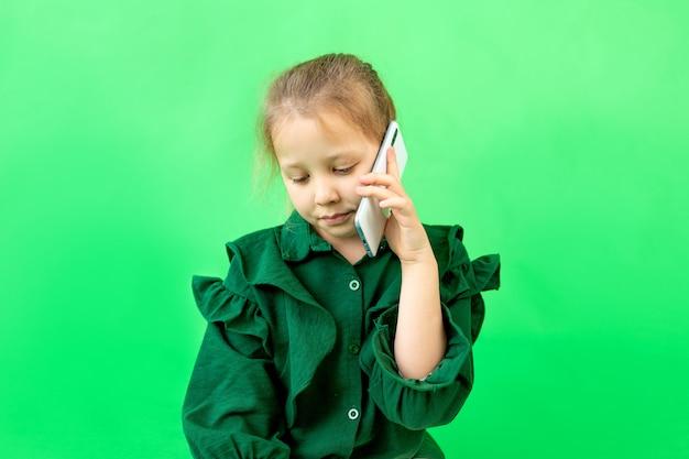 Девочка 8 лет сидит и разговаривает по телефону