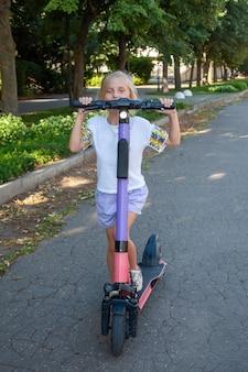 公園で借りた電動スクーターに8歳の女の子が乗る。キックスクーターの共有