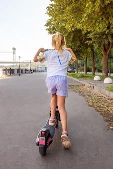 公園でレンタルの電動スクーターに乗る8歳の女の子