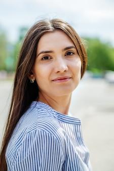 街の通りにアジア人の姿をした女の子。ぼやけた背景に若いタタール人の夏の肖像画
