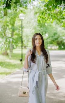 都市公園の散歩にアジアの外観の女の子。緑の葉を背景に若いタタール人の夏の肖像画