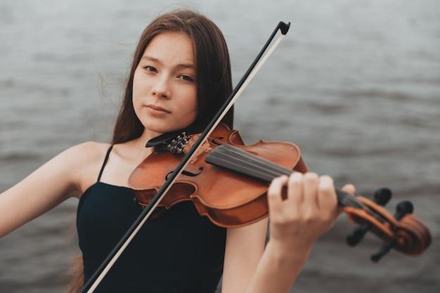 Девушка азиатской внешности играет на скрипке на природе. фото высокого качества
