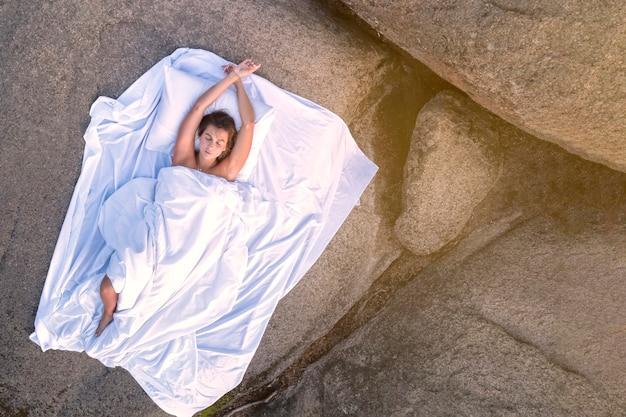 ヨーロッパ風の女の子が白いシートの山頂で眠ります。コピー用のスペース。山の空気と自然の中での健康的な健康的な睡眠、リラクゼーションと瞑想的な快適さ。