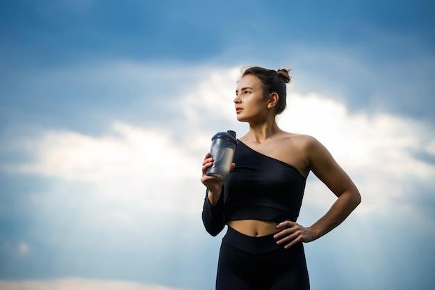 Девушка европейской внешности со спортивным телосложением в черном топе и черных леггинсах на фоне голубого неба. она пьет воду из бутылки. здоровый образ жизни, атлетичная девушка брюнет. мотивация к спорту