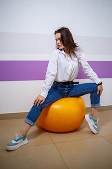 그녀의 얼굴에 다른 감정을 가진 유럽 외모의 소녀는 체조 선수를 위해 공에 앉아 있습니다. 웃 고 장난 하는 매력적인 젊은 갈색 머리 여자