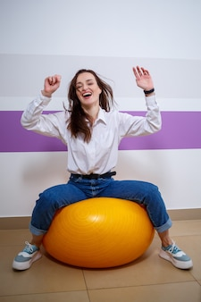彼女の顔にさまざまな感情を持つヨーロッパの外観の女の子は、体操選手のためにボールに座っています。魅力的な若いブルネットの女性の笑顔と浮気