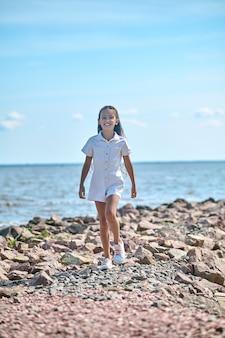 Девушка на пляже. девушка в белом платье гуляет по пляжу