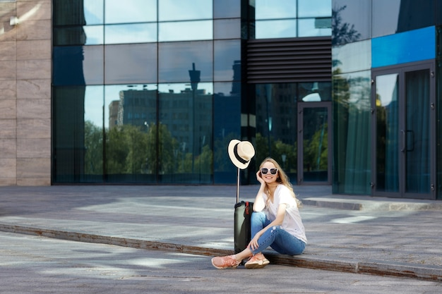 Девушка в пути с чемоданом и соломенной шляпой сидит недалеко от аэропорта, летние каникулы
