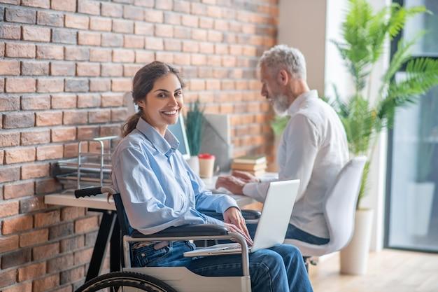 Девушка в инвалидной коляске разговаривает со своим коллегой-мужчиной и выглядит вовлеченной