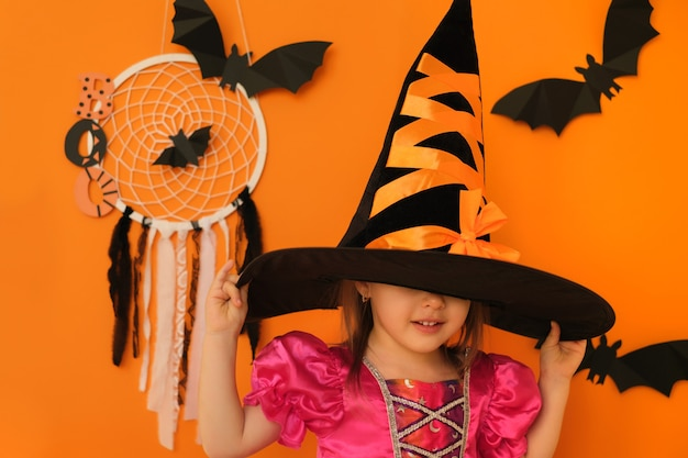 オレンジ色のスタジオの背景にある女の子は、ハロウィーンのために魔女の帽子をかぶって、その下に顔を隠しています