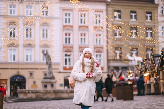 冬の街を背景に女の子雪に覆われた街の路上で美しい若い幸せな女の子