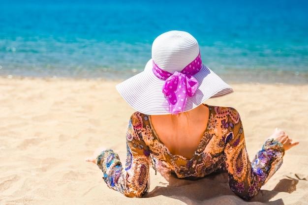 바다 배경 근처 모래에 소녀. 휴가 여행에 모자와 함께 행복 한 여자입니다.