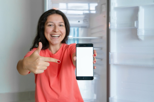 한 소녀가 스마트 폰으로 음식을 주문합니다. 음식이없는 빈 냉장고. 음식 배달 서비스 광고.