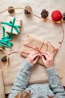 Девушка упаковывает книгу в подарок, заворачивает в крафт-бумагу и перевязывает красной веревкой. рождественские и новогодние подарки к празднику