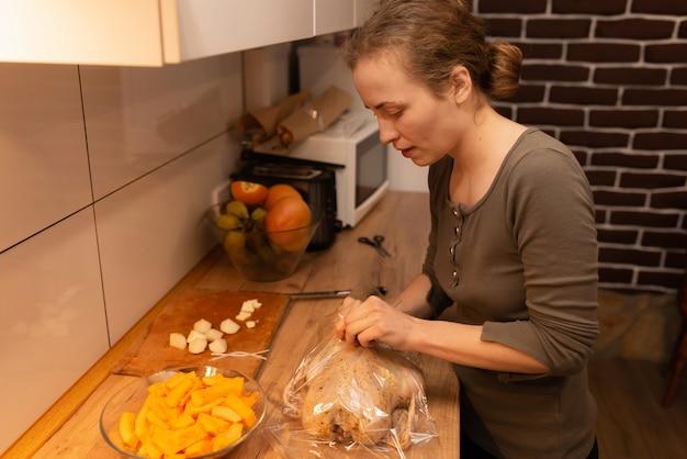 Девушка упаковывает курицу, маринованную со специями, в рукав для запекания