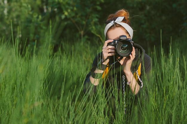 한 여자 사진가가 손에 전문 사진-비디오 카메라를 들고 있습니다. 아름다운 녹색 자연과 숲을 배경으로.