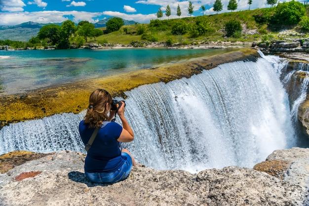 Девушка-фотограф фотографирует ниагарский водопад в черногории.