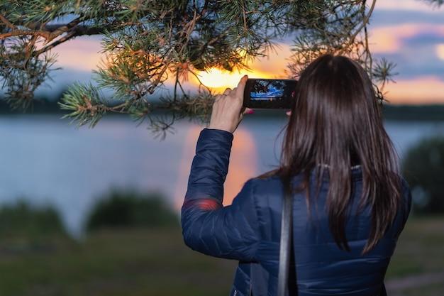 女の子が電話で湖に沈む夕日を撮影