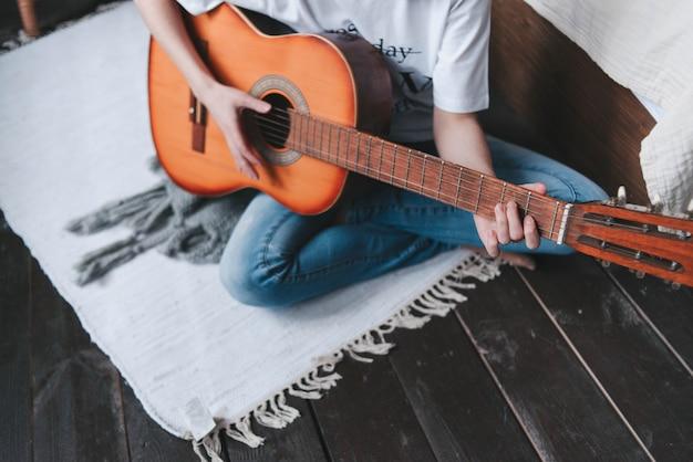 소녀는 나무 기타, 클로즈업을 재생합니다. 기타 연주. 손에 기타